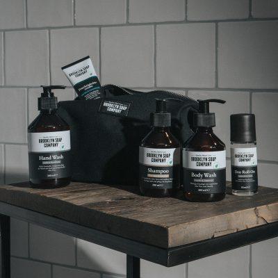 Schwarze, edle Kulturtasche mit verschiedenen Naturkosmetik Produkten für Männer