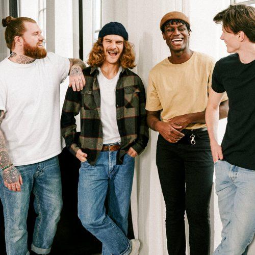 Naturkosmetik, vier attraktive Männer mit und ohne Bart stehen lachend im Halbkreis